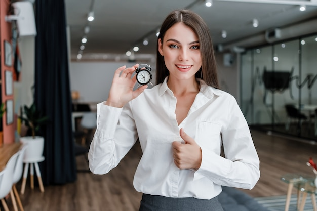 Woman in the office manages her time with alarm clock