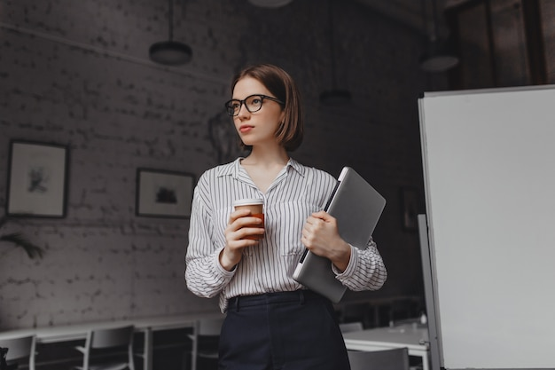 Woman in office pants and shirt poses with cup of coffee and holds laptop. shot of short-haired girl in glasses in bright office.