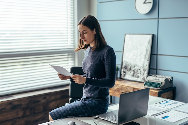 Woman in the office reading documents sitting on a table.