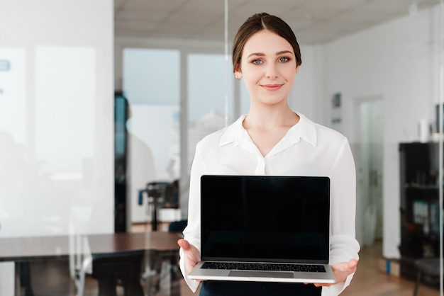 Woman in the office showing blank laptop screen