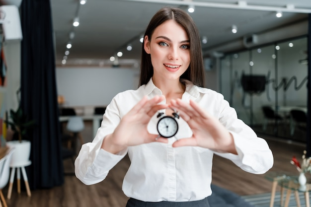 Woman in office with alarm clock smiling