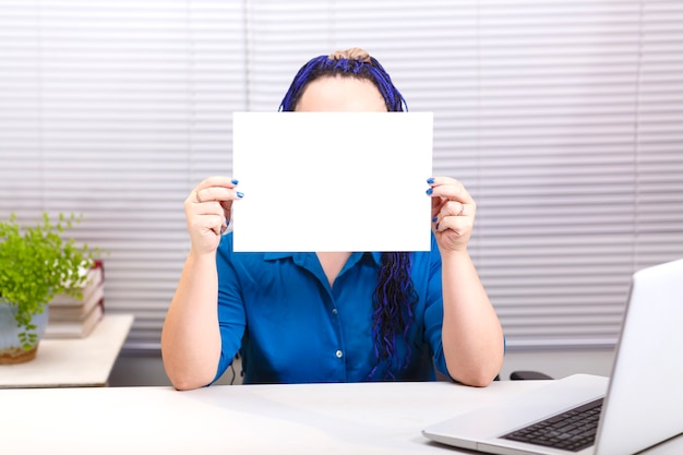 A woman in the office with blue afro braids at the computer holds a horizontal plate in her hands