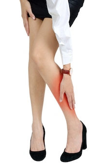 Woman office worker on high heels holding her calf with red highlight in pain area.