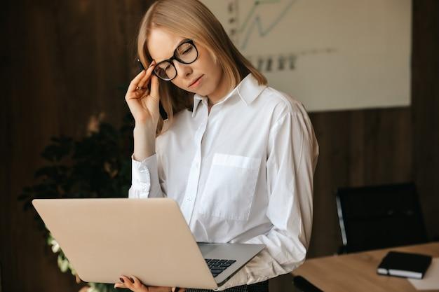 여성 회사원은 사무실에서 인터넷에서 작업하는 노트북에서 어려운 작업을 수행합니다.