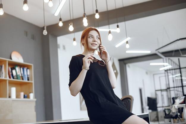 Donna in ufficio. lavoratore tallking. signora in un vestito nero.