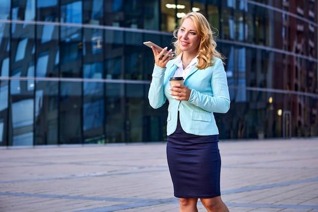 手にコーヒーを持っている女性サラリーマンはスピーカーフォンで電話で話します