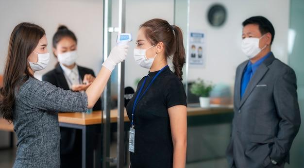 Женщина-офицер использует термометр сканера для проверки температуры всего человека, прежде чем перейти в офис внутри для работы