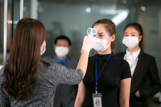 여성 장교 사용 스캐너 온도계는 작업을 위해 내부 사무실에 전달하기 전에 모든 사람의 온도를 확인합니다.