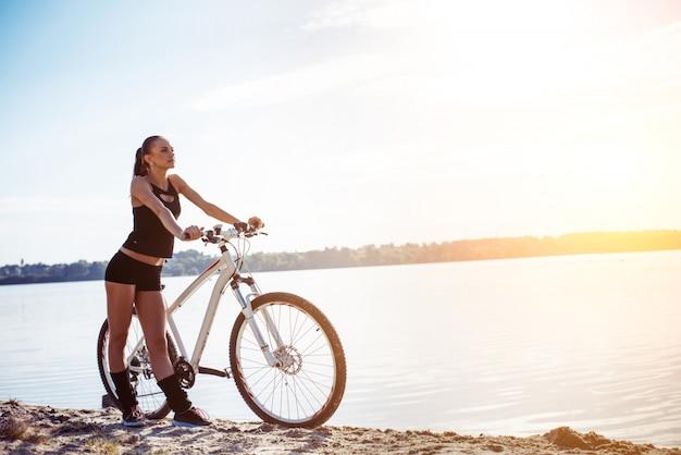 水の近くの自転車の女性