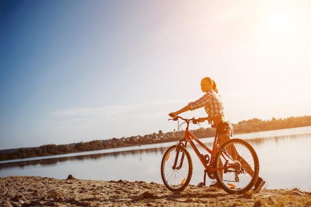 Женщина на велосипеде у воды