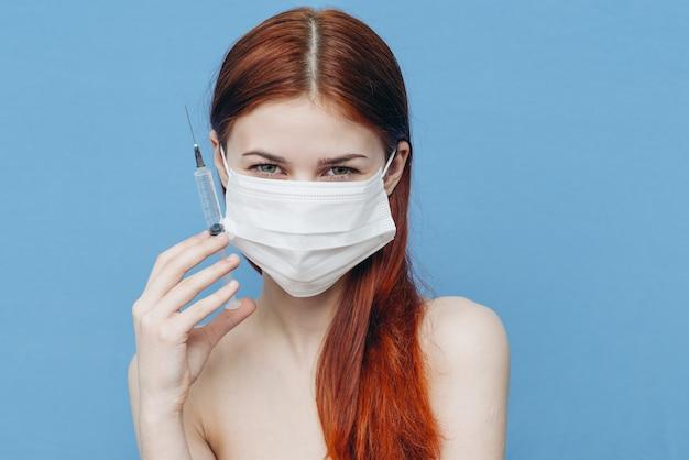 Женщина на синем фоне в медицинской маске и шприцах в руке, уход за красотой инъекции ботокса