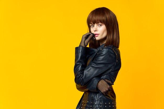 黒い服と手袋で明るい黄色の背景の女性