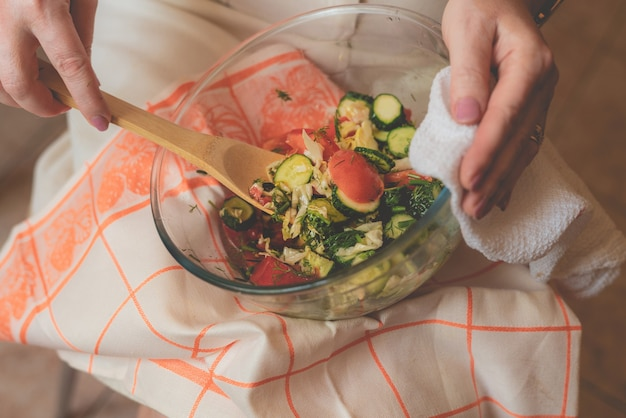 그녀의 무릎에 원시 샐러드 접시와 함께 다이어트에 여자. 해독 건강한 개념