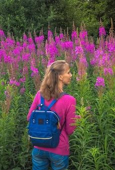 花畑の柳のハーブの女性。軽いバックパックで旅行のコンセプト。