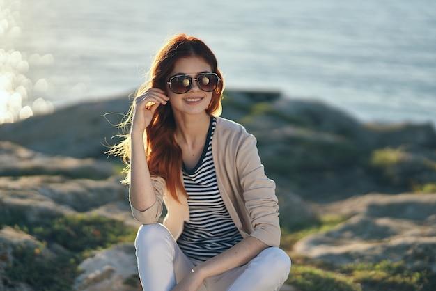 海の近くの山の高い石の上の女性と彼女の顔の眼鏡夏休み旅行