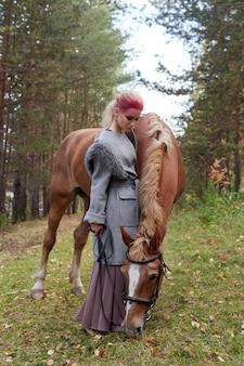 秋に馬の女性。女の子の顔、髪の色に創造的な明るいピンクのメイク。馬と少女の肖像画。秋の森での乗馬。秋服