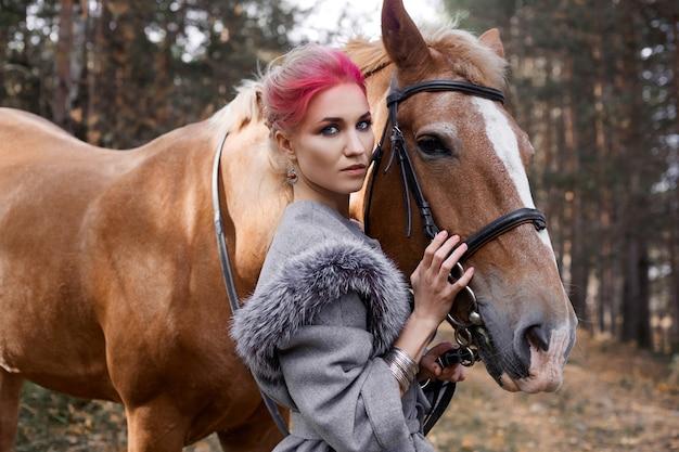 Женщина на лошади осенью. креативный ярко-розовый макияж на лице девушки, окраска волос. портрет девушки с лошадью. катание на лошадях в осеннем лесу. осенняя одежда