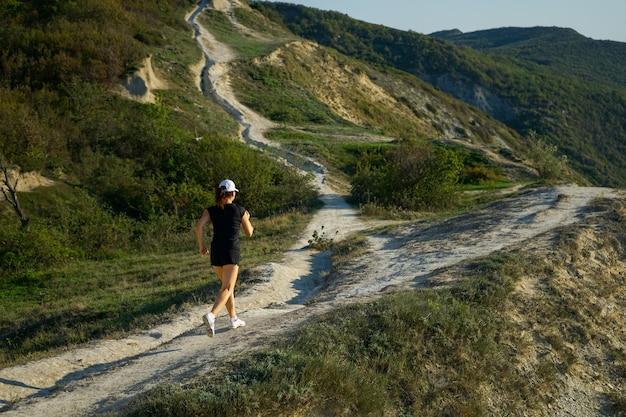 海の海岸の山でジョギング旅行中の女性