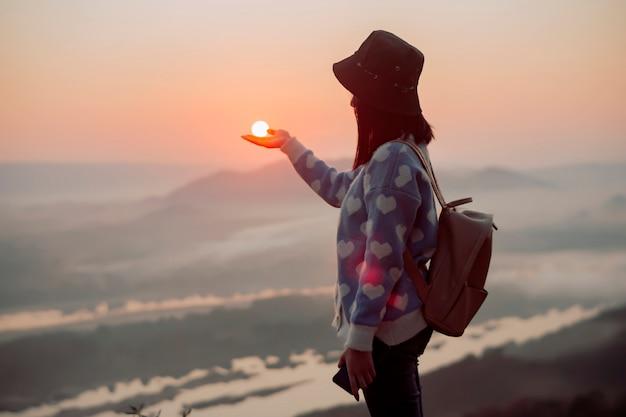 太陽を保持している山の上の女性