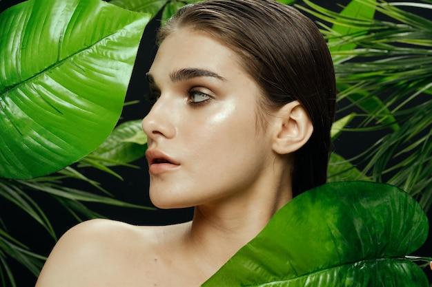 緑のジャングルの上の女性はエキゾチックな裸の肩を残します