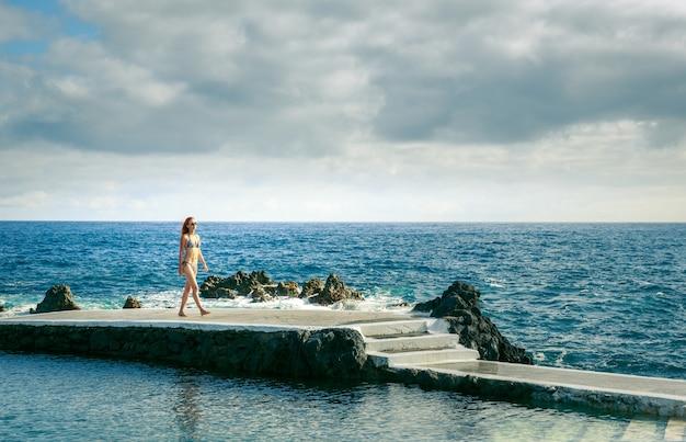 海の桟橋にいる女性