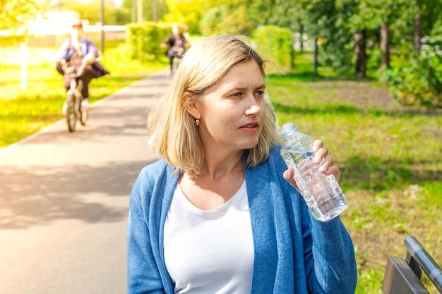 화창한 더운 날에 여자가 공원에서 물을 마시러 가는 동안 병을 들고
