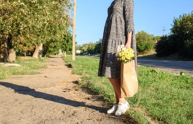美しい花のクラフトバッグを持って秋の日の散歩の女性。菊の花が入ったエコバッグ。