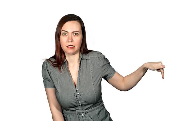흰색 배경에 있는 여성은 얼굴에 혐오감을 표시하면서 무언가에 손가락을 보여줍니다.