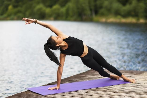 川の近くの木造の橋の上の女性は、賢人のポーズを実行するヨガのアーサナを練習します