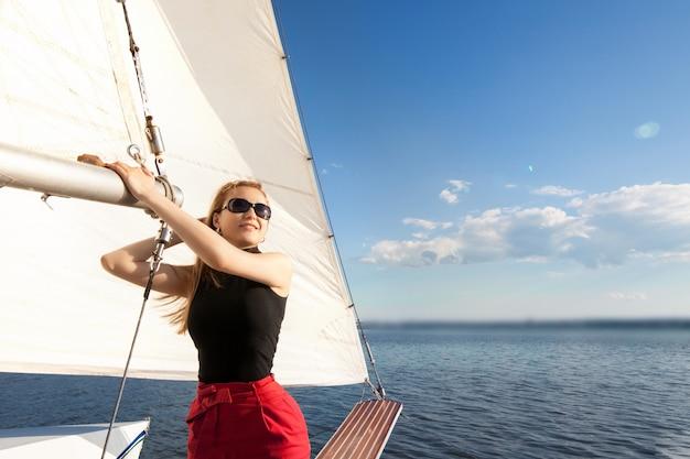 Женщина на яхте, против паруса неба и моря. концепция яхтинга и морского отдыха.