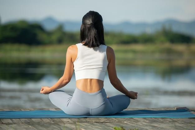 Женщина на коврике для йоги, чтобы расслабиться в парке у горного озера. спокойная женщина с закрытыми глазами, практикующая йогу, сидящая в позе падмасана на коврике, упражнения лотоса, привлекательная спортивная девушка в спортивной одежде.