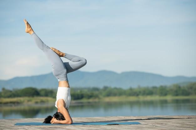 Женщина на коврике для йоги, чтобы расслабиться в парке. молодая спортивная азиатская женщина занимается йогой, делает упражнения стойки на голове, тренируется, носит спортивную одежду, брюки и топ.