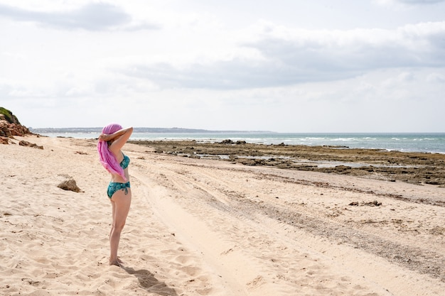 ピンクのヘッドスカーフ、癌を結ぶビーチの女性