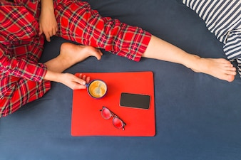 Woman on bed with coffee and smartphone