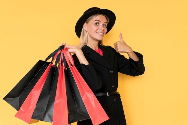 黒い金曜日の販売の女性は袋でジェスチャーを親指します。