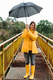 Женщина на мосту держит зонтик