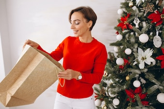 Woman on christmas with gifts by christmas tree