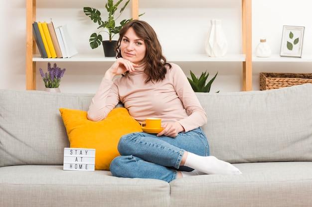 ソファでお茶を飲む女性