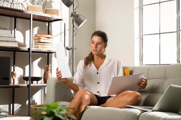 紙を保持しているソファの上の女性