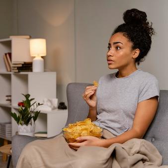 Женщина на диване смотрит телевизор и ест чипсы