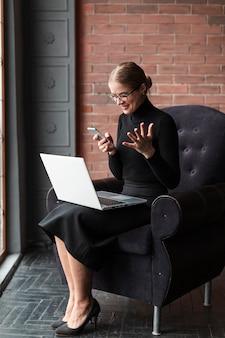 Женщина на диване с ноутбуком и мобильным