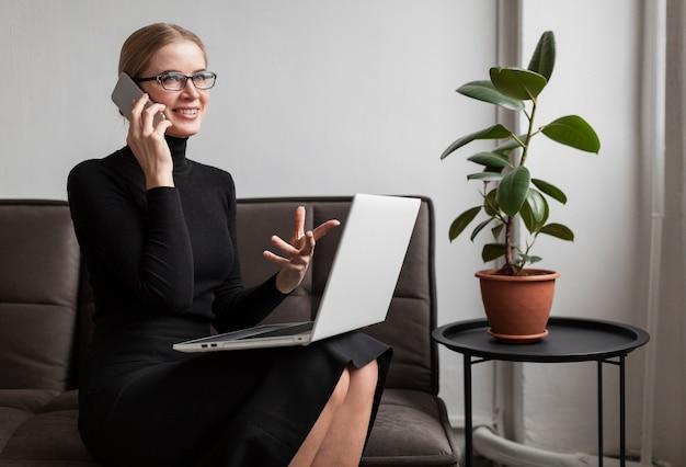 ノートパソコンと携帯電話とソファの上の女性
