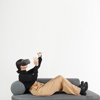 バーチャルリアリティヘッドセットとソファの上の女性
