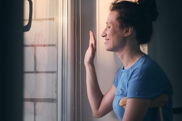 목발을 짚고 창가에 서서 손을 흔드는 여성