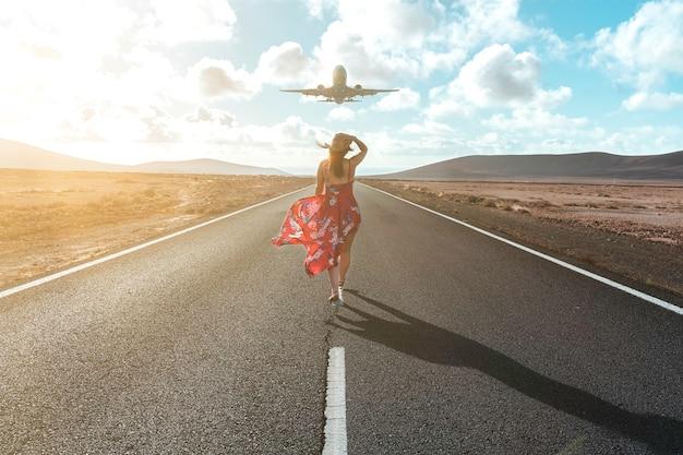 착륙할 비행기를 바라보는 사막의 여성 - 여행 개념
