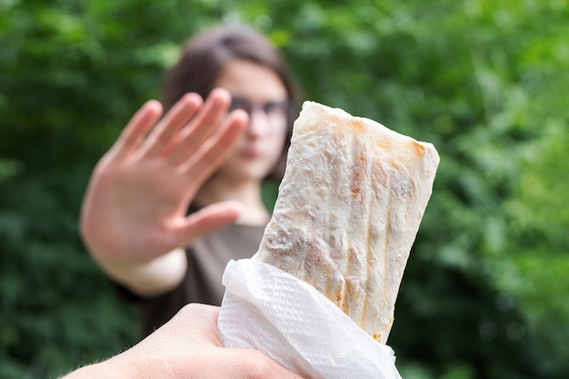 웰빙 개념에 대 한 다이어트에 여자입니다. 여자는 정크 푸드나 지방이 많은 패스트푸드 샤와르마를 거부하기 위해 손을 내미는 신호를 보낸다. 저렴한 음식 개념입니다. 건강 식품 개념