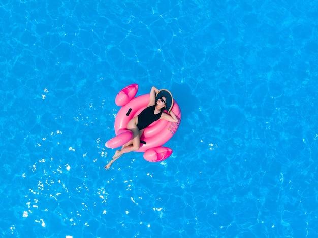 호텔 수영장에서 플라밍고 수영장 플로트에 여자