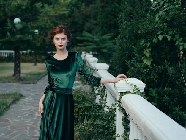 Женщина на перилах прогулки зеленого платья природного парка
