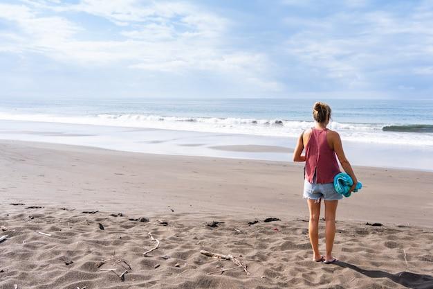 바다를 바라보는 황량한 해변에 등을 대고 있는 여자