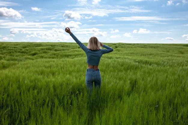 팔을 쭉 뻗고 등을 대고 있는 여자 밀밭 한가운데 있는 날씬한 젊은 여성 푸른 잔디의 밝은 필드 구름과 푸른 하늘